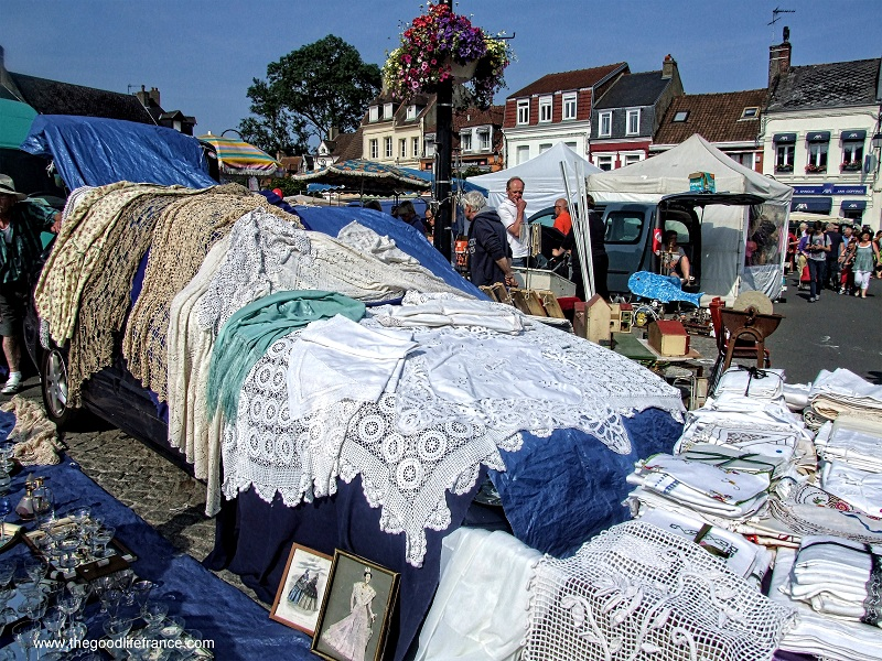Stall at a flea market in France piled high with textiles