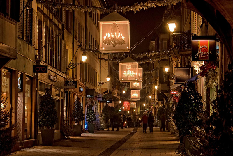 Street in Strasbourg lit up for Christmas with Chandeliers hanging over the cobbled road