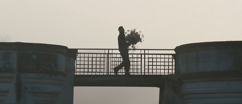 Man crossing a drawbridge at the Castle of Chenonceau carrying a bouquet of flowers