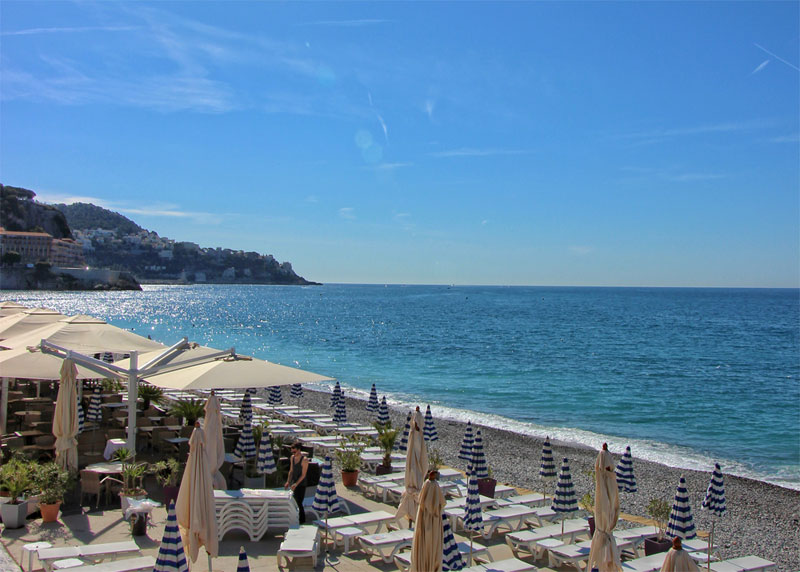 The pebble beach at Nice, France on a very sunny day, parasols over tables provide shade