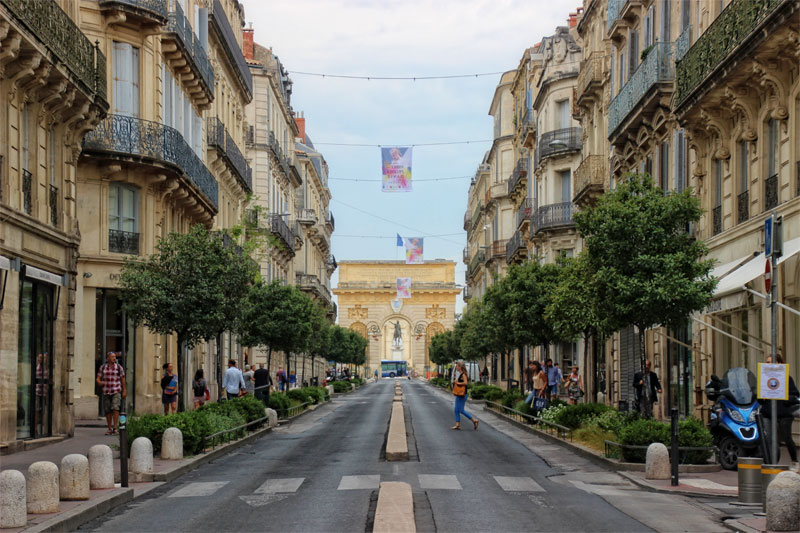 Promenade du Peyrou, Montpellier a long street lined with tall buildings with an arch at the end
