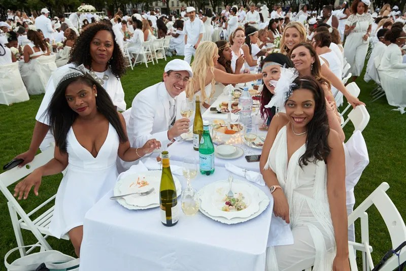 Smiling diners dressed in white for the Diner en Blanc Paris picnic