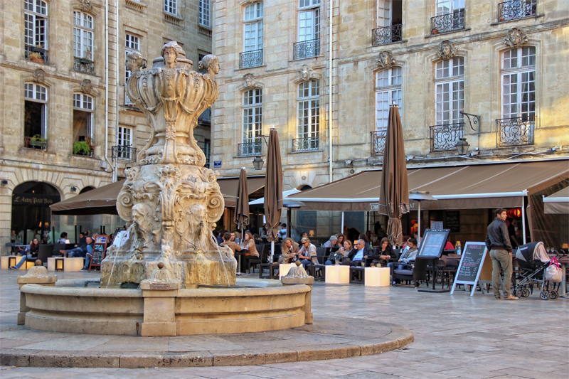 Small square in Bordeaux city, lined with shops and bars, a central fountain spurts water