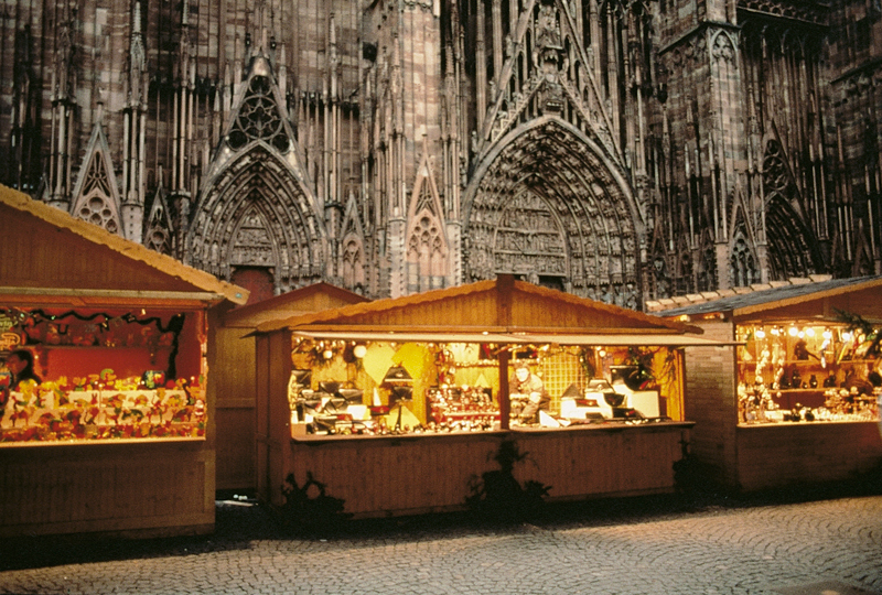 Christmas chalets lit up for Christmas in front of the Gothic cathedral of Strasbourg