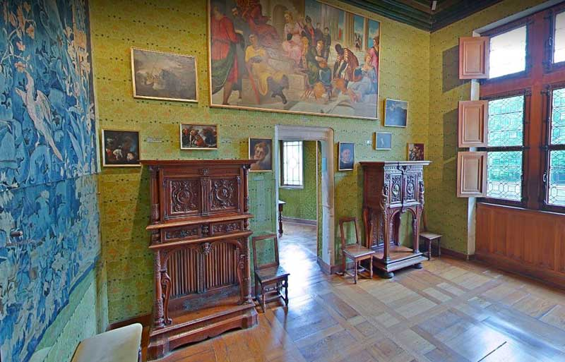 Room with wooden cabinets , paintings and rich tapestries at the Chateau de Chenonceau