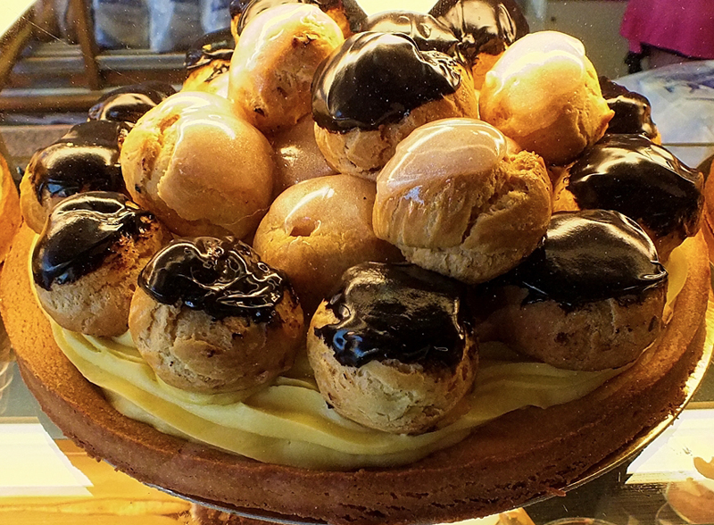 Cake consisting of choux buns called profiteroles drizzled with chocolate and filled with cream