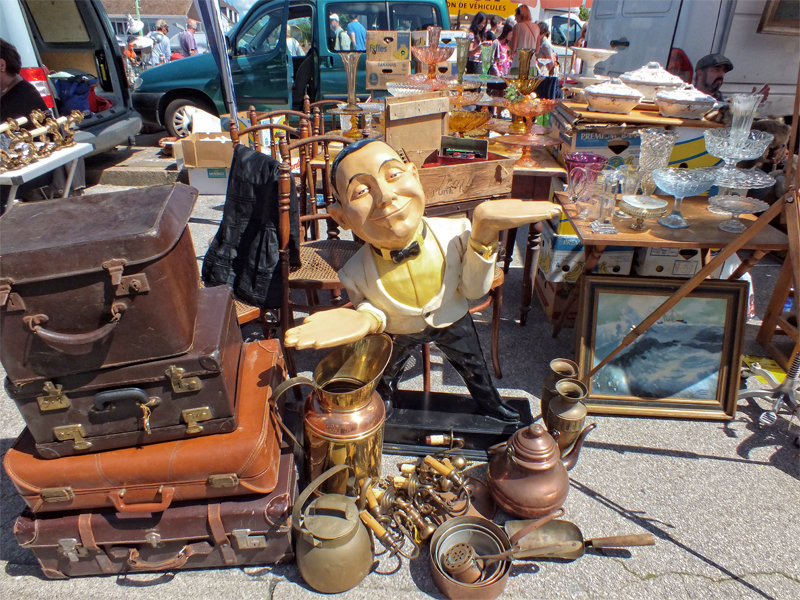 Stall at a flea market in France - old leather suitcases, china and copperware