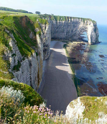 Looking over the impressive rock formations and wild flower covered cliffs of Etretat, Normandy