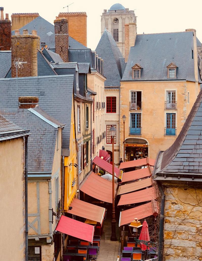 Vue sur les rues du Mans avec des toits en ardoise grise de bâtiments en pierre moelleux et des auvents rouges colorés des magasins