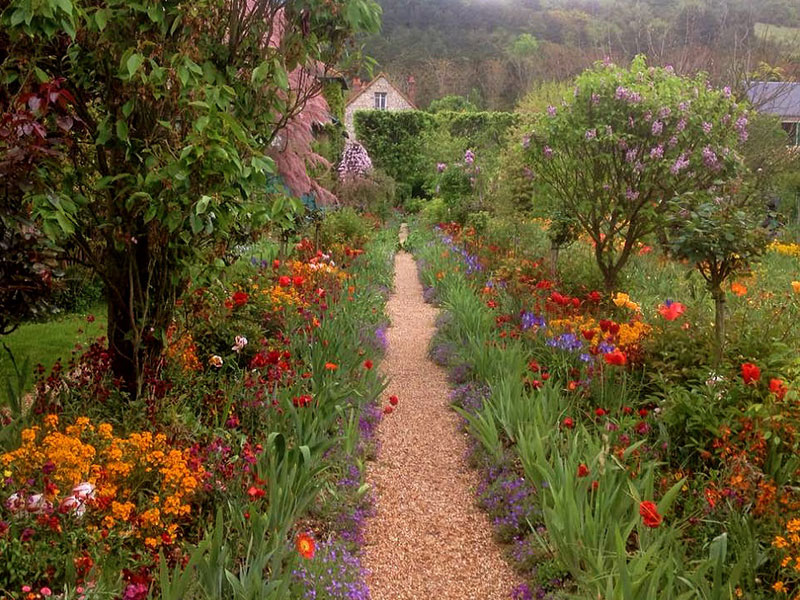 Garden filled with a riot of colourful flowers at Monet's house, Giverny, Normandy