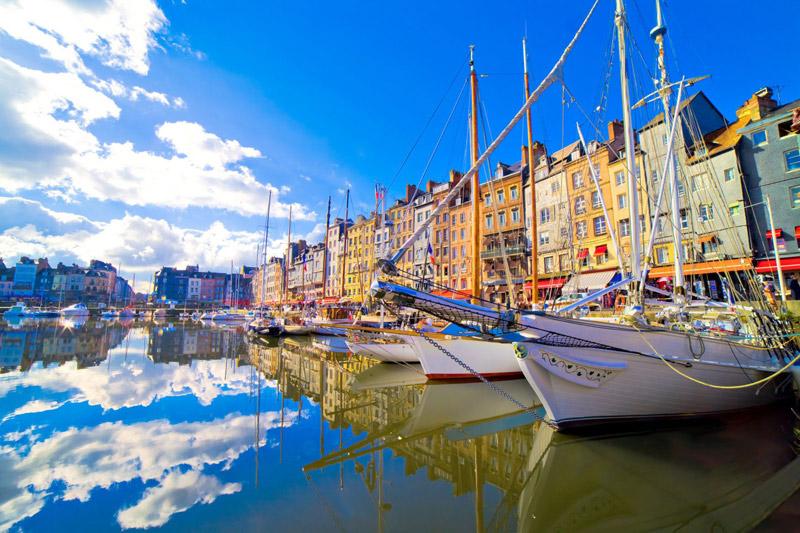 Día soleado en el puerto de Honfleur, Normandía, los pequeños barcos suben y bajan, los altos edificios bordean el puerto