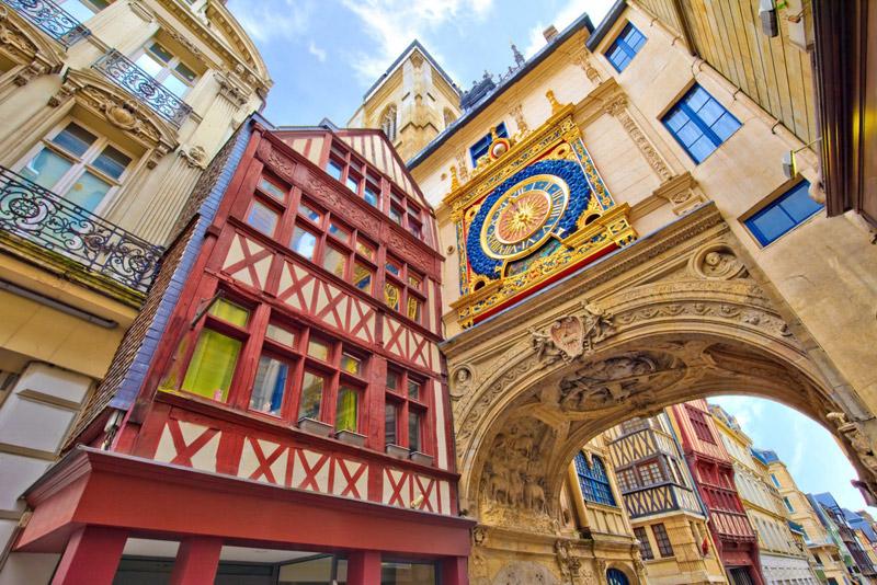 Casas de entramado de colores en la ciudad de Rouen, Normandía, un paseo arqueado con un reloj antiguo