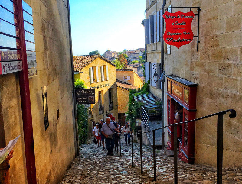 People climb a steep hill, hauling themselves up by handrails in Saint-Emilion