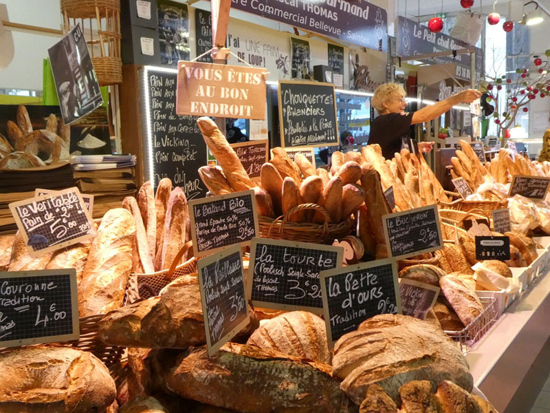 Woman at a bread stall in the market of Saintes, France with a huge choice of loaves