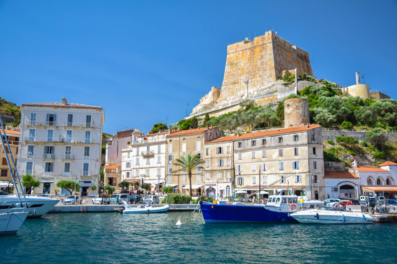 Beautiful harbour in Corsica, boats floating on calm, crystal clear waters, palm trees grow round the edge of the water