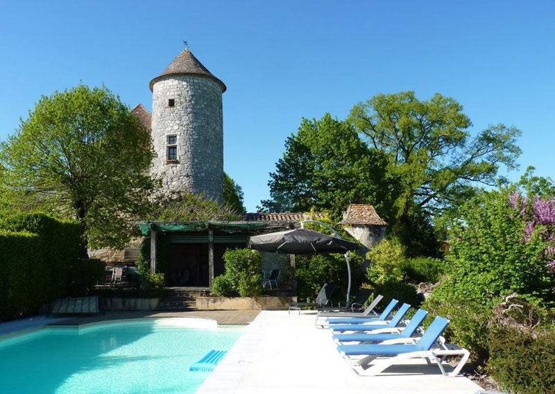 Swimming pool in the grounds of a chateau with a fairy-take like tower in the background
