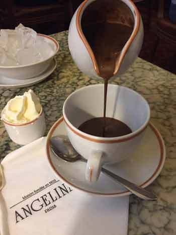 Pouring hot chocolate from a jug into a cup in a cafe in Paris