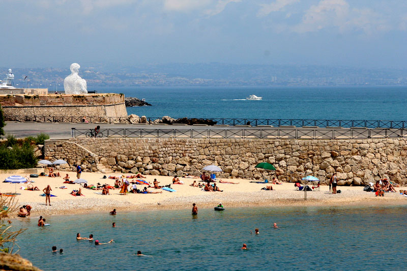 Beach scene, golden sand, people swimming in the sea at Antibes, southern France
