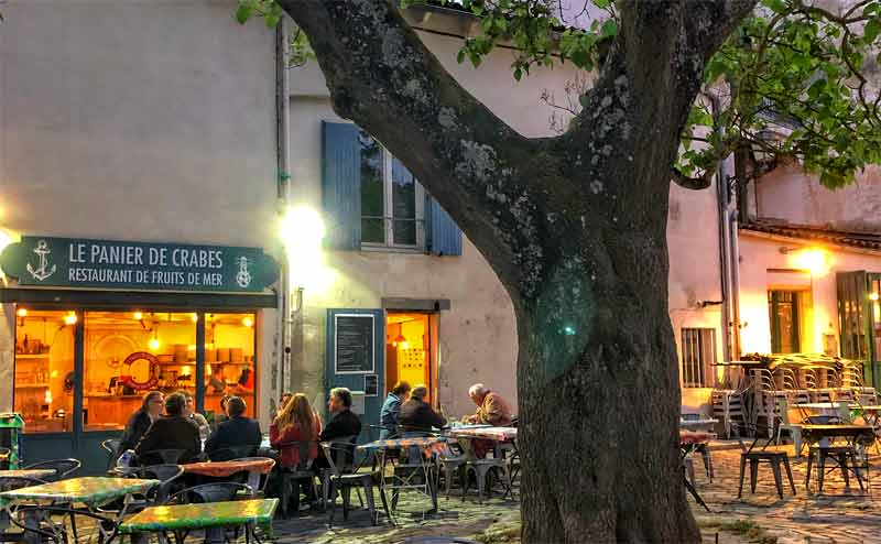 Small square with a leafy tree and a tiny restaurant with people eating at tables on a terrace in La Rochelle