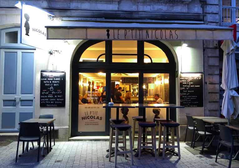 Front of the P'tit Nicolas restaurant, welcoming light from inside on a dark night