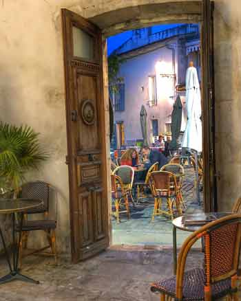 Looking through a grand wooden door of a courtyard at a terrace lit by pretty lights, bar in La Rochelle