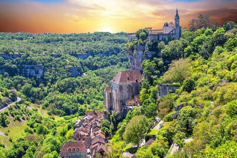 Village of Rocamadour seems to cling to a cliff top surrounded by forests