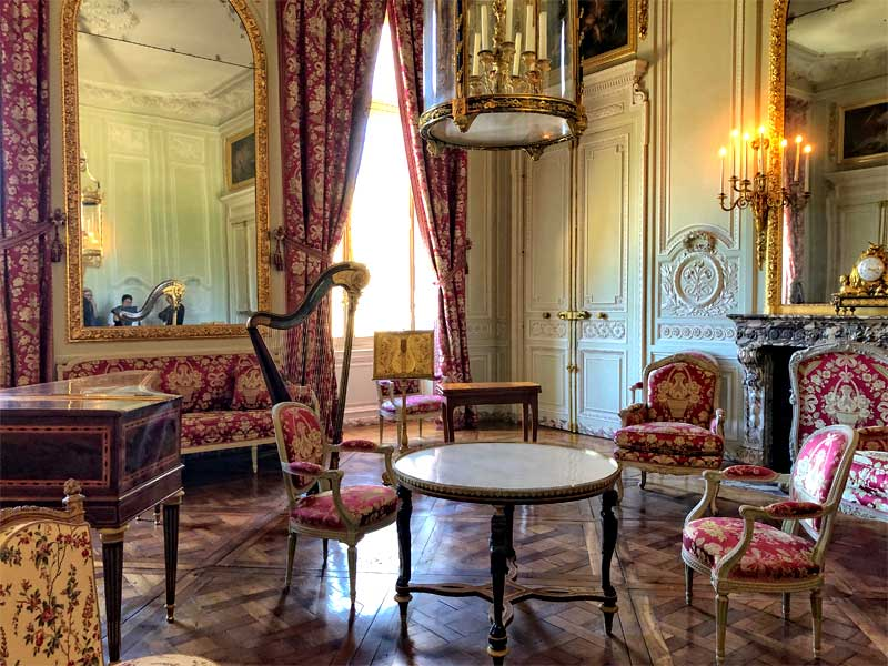Room in chateau of Verailles, embroidered textiles on walls and chairs, chandeliers and carved wood panels