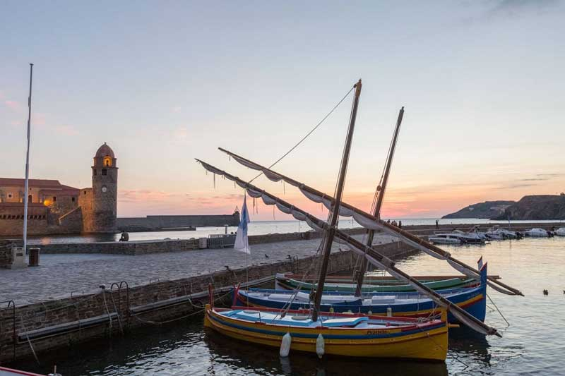 View of the Collioure coastline, boats floating in the port at sunset
