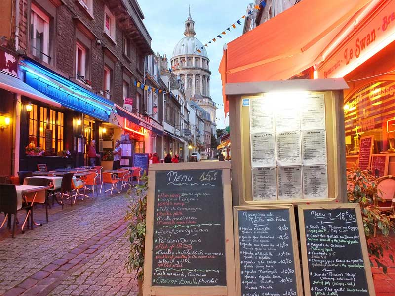 Cobbled street in Boulogne-sur-Mer, a domed church tower at one end, restaurants line the street