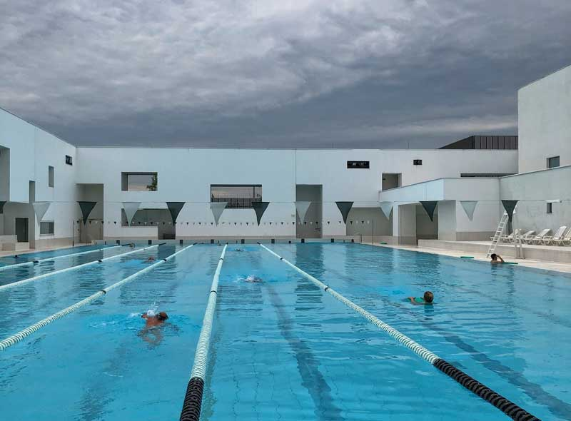 Art deco swimming pool in white stone against a dramatic stormy sky in Le Havre