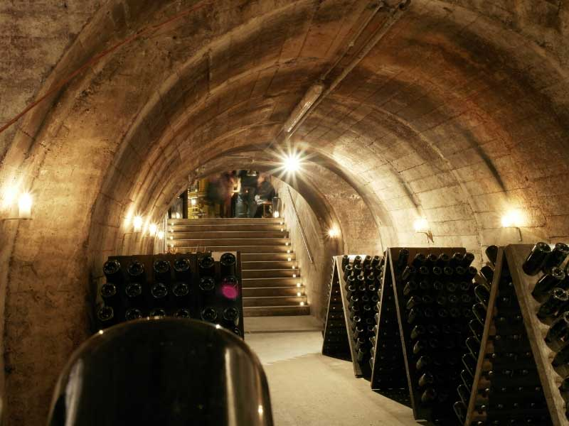 Inside a dimly lit cellar, bottles of Champagne in shelves ready for turning as they mature
