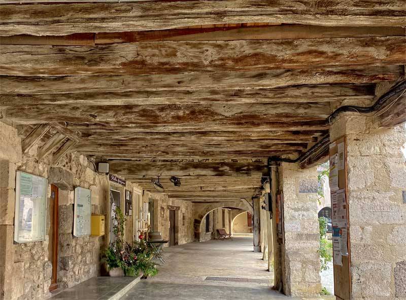 Medieval arcade with a stone walkway and wood timbered ceiling in Fources