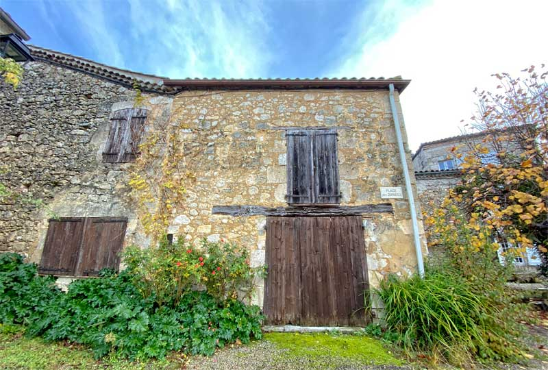 Medieval house with thick stone walls and wooden shutters in Fources, Gers