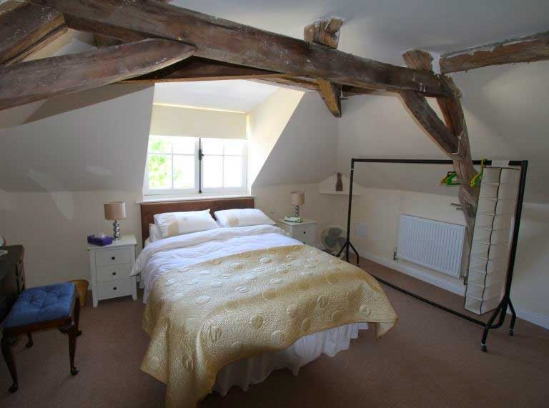 Bedroom with wood beams on ceiling in an old house near Saumur, Loire