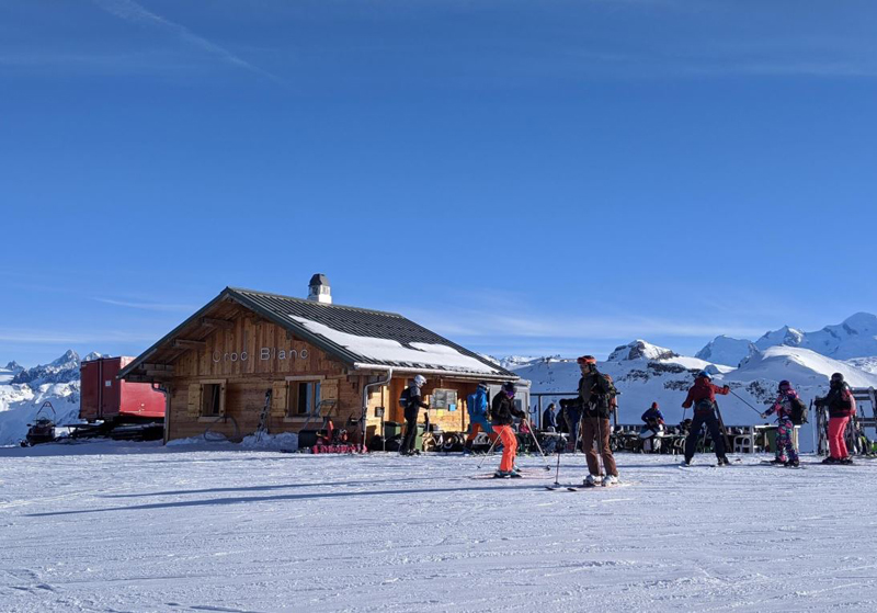 Skiers by a restaurant chalet in the mountains of Samoens French Alps