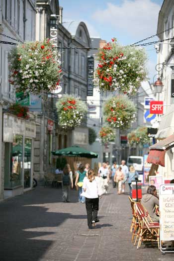Streets filled with baskets of flowers in Cognac, cafe tables and chairs on cobbled streets