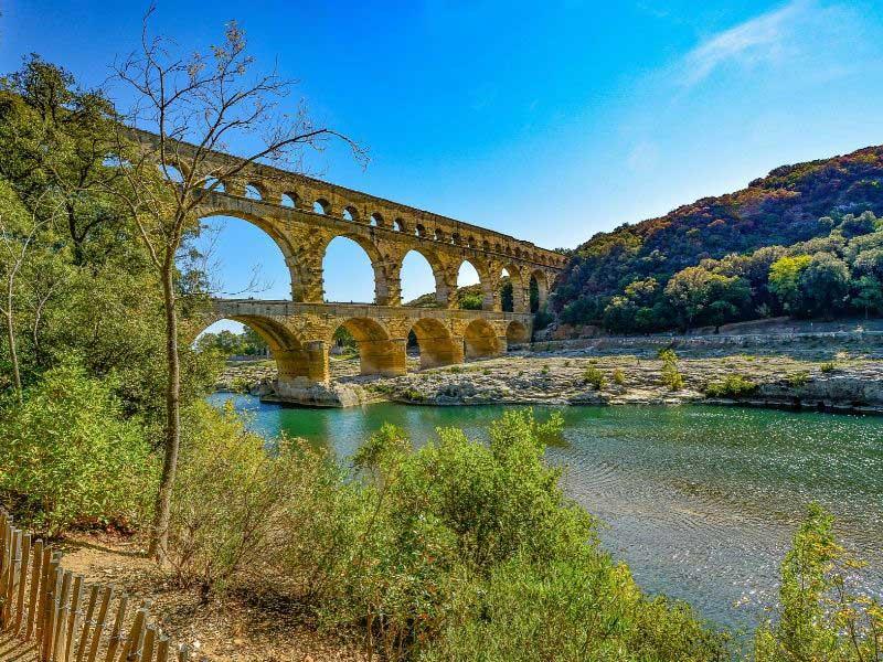 Tall three tier Roman aqueduct of Pont du Gard straddles a river under a blue sky