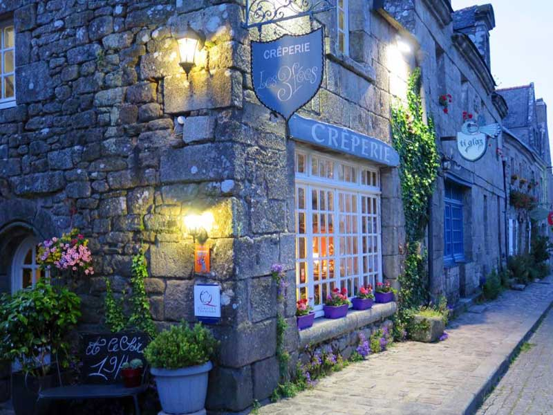 Creperie, pancake, restaurant in a cobbled street in Locronan, Brittany, at dusk