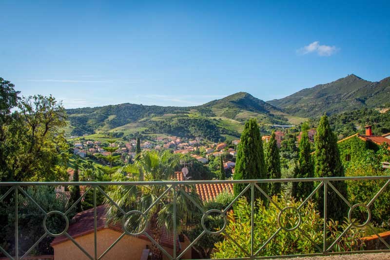 View over the countryside of Collioure, grassy and forested hills, tiny villages in valleys