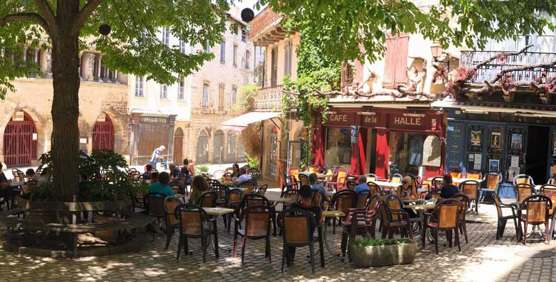People sitting at a terraced cafe on a sunny day under the shade of plane trees