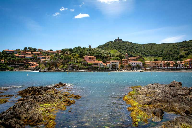 Colourful villas line the shore of the bay of Collioure, southern France, forested hills in the background