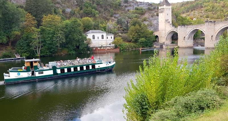 Boat passing under a stone bridge, Tarn-et-Garonne, France