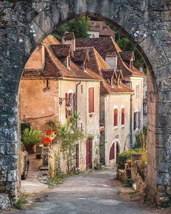 View through a stone archway of a cobbled street lined with old houses, roses climbing up the walls