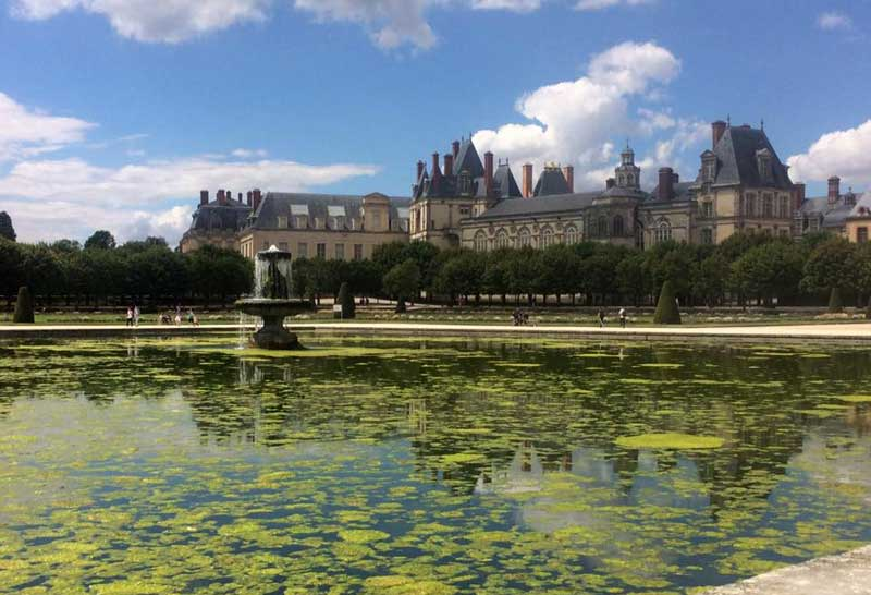 Chateau de Fontainebleau surrounded by beautiful gardens with lakes and fountains