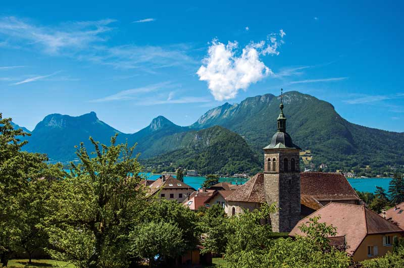 Outline of a village against a clear mountain lake, Talloires, Annecy Mountains