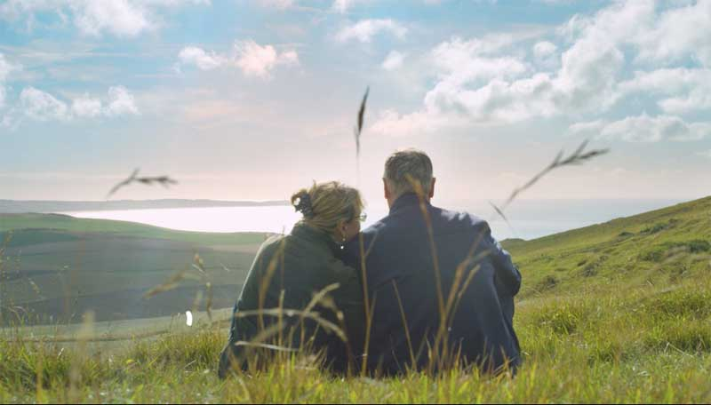 Couple sitting on a grassy hill overlooking the English Channel from the Opal Coast, France