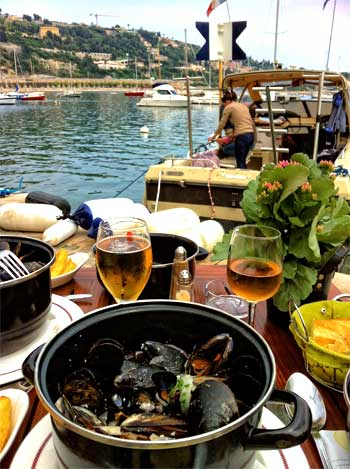 View of Cap Ferrat from Villefranche-sur-Mer across the sea from a cafe serving mussels and chips