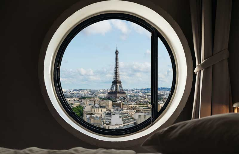 View from a round window over Paris and the Eiffel Tower