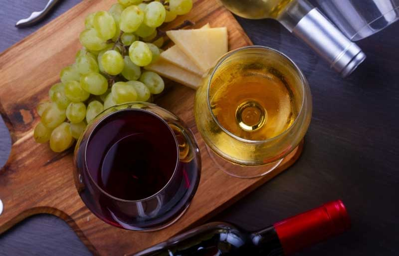 Glass of red wine and glass of white wine with some grapes and cheese on a wooden board