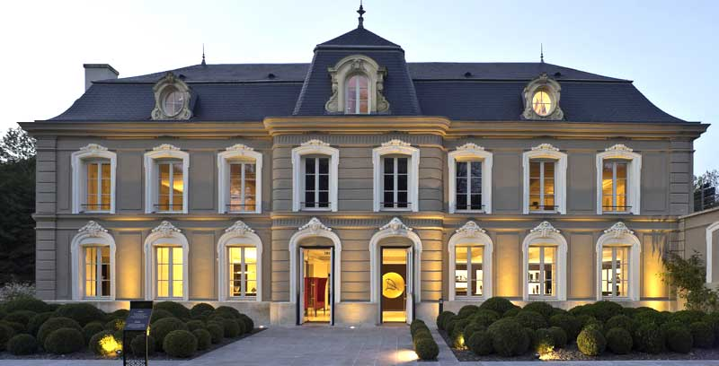 Facade of a small chateau, the headquarters for Champagne Devaux, windows lit at night